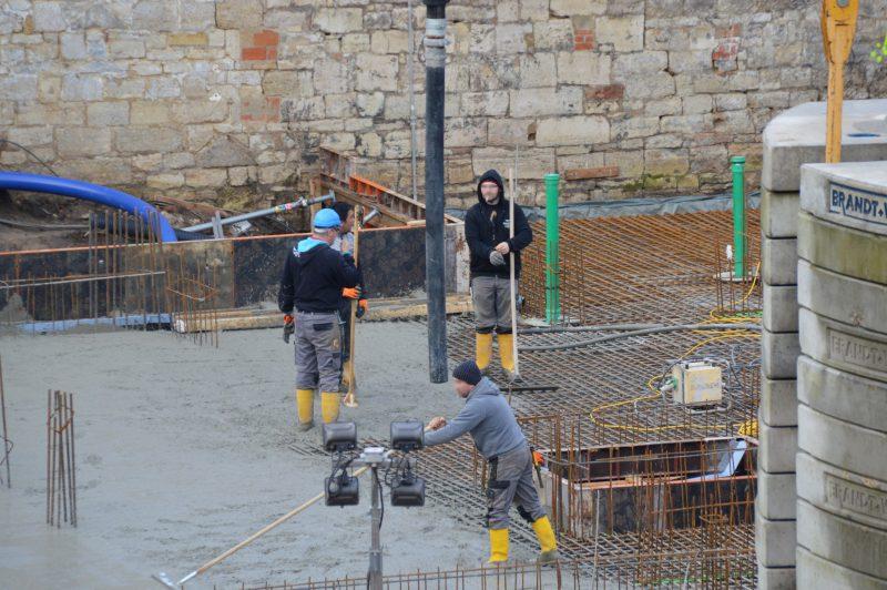 Bauarbeiter beim Guss der Bodenplatte für den Neubau der Gedenkstätte
