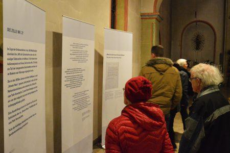 """Nach dem Gottesdienst. Die Besucher_innen informieren sich über die Geschichte des """"Grauen Hauses"""" / Lukkas Busche"""